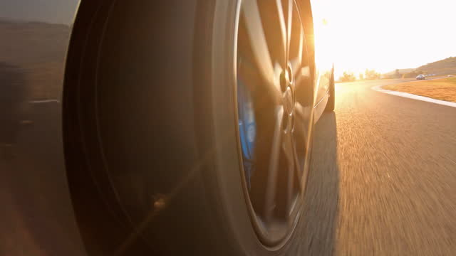 closeup view of sports race car wheel spinning, driving on motor racing track at sunset - accelerator pedal stock videos & royalty-free footage
