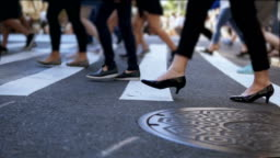 Close-up view of stylish female feet. Businesswoman crossing the road in crowded downtown. Slow motion