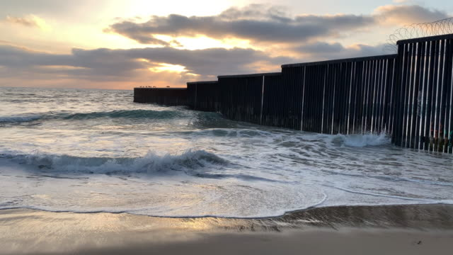 a close-up view of the beach and waves at sunset near the international border wall  in playas tijuana, mexico - surrounding wall stock videos & royalty-free footage