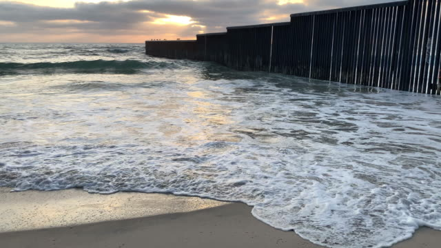 a close-up view of the beach and waves at sunset near the international border wall  in playas tijuana, mexico - international border stock videos and b-roll footage