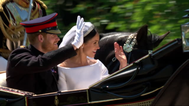 vidéos et rushes de close-up view of the newlywed duke and duchess of sussex travelling by horse-drawn carriage along the long walk, windsor great park. - couple marié