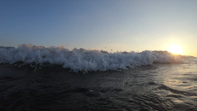 close-up view of wave by sunset slow motion - foam material stock videos & royalty-free footage