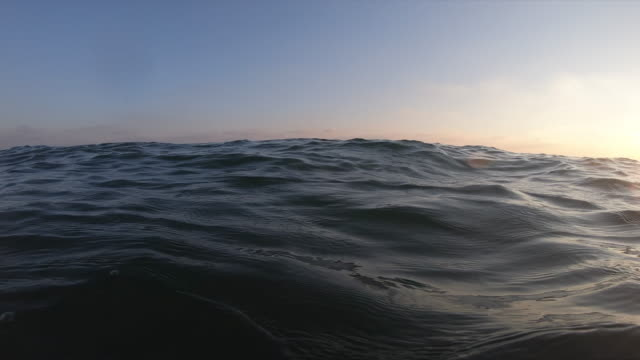 close-up view of wave by sunset slow motion - ocean tide stock videos & royalty-free footage