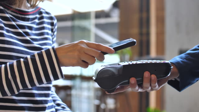 close-up view of woman paying a nfc transaction with a smartphone in shop - acquisto con carta di credito video stock e b–roll