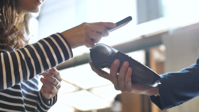 vídeos de stock e filmes b-roll de close-up view of woman paying a nfc transaction with a smartphone in shop - pagar