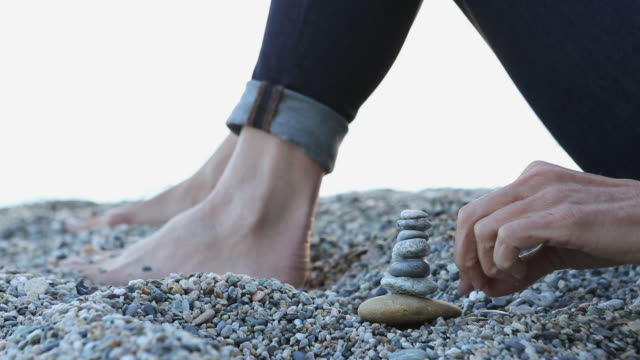 Close-up view of woman stacking pebbles, on beach