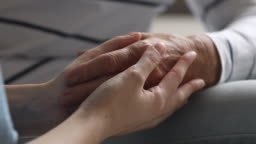 Closeup view of young female hands holding old grandma arm