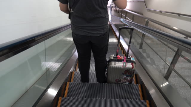 vídeos de stock e filmes b-roll de close-up view of young stylish man with suitcase standing on the escalator. feet of attractive man on the airport - pé