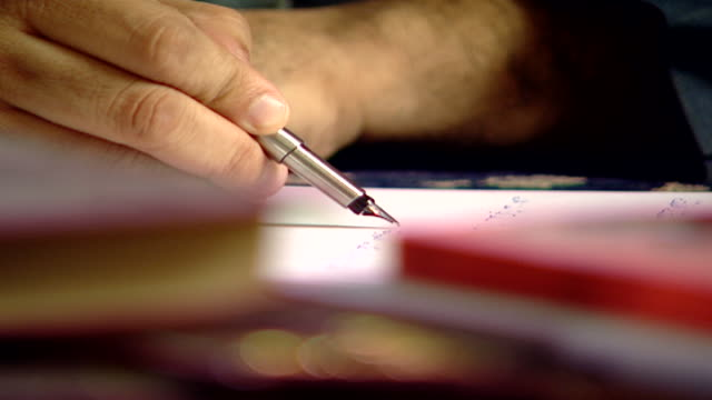 closeup view through books on a desk of a man's hand writing on paper in arabic with a fountain pen - pen stock videos & royalty-free footage