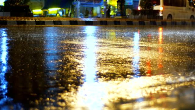 Primer plano agua mientras la lluvia en la calle con la reflexión de la luz