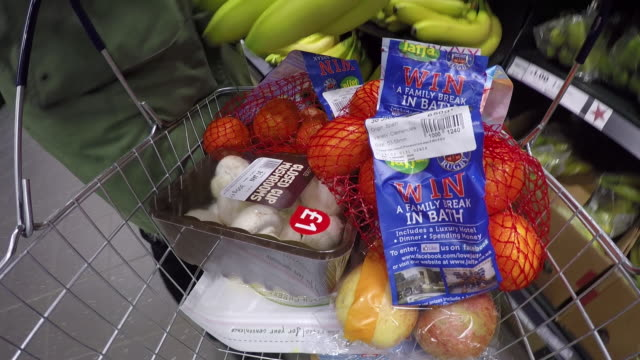 Close-up, wearable camera shot of a hand loading fruit into a shopping basket at a large UK supermarket.