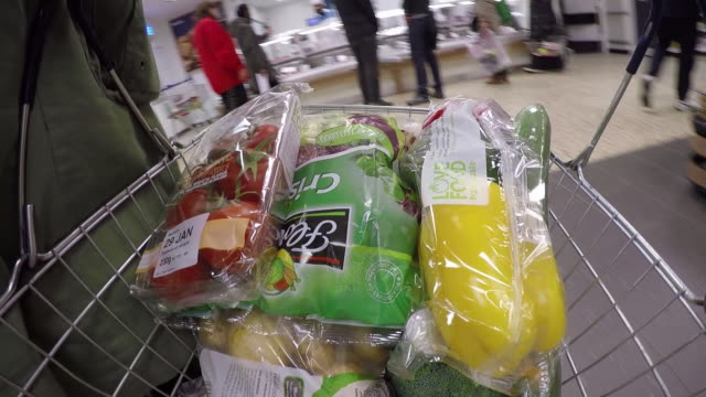 close-up, wearable camera shot of various vegetables being added to a shopping basket at a large uk supermarket. - tomato stock videos & royalty-free footage