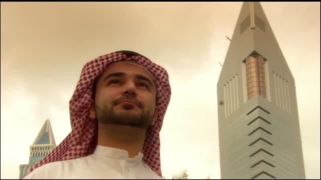 stockvideo's en b-roll-footage met close-up - wide shot arab man standing near jumeirah emirates towers hotel/ dubai, united arab emirates - 2007