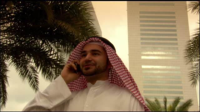 Close-up - wide shot Arab man talking on cell phone near Jumeirah Emirates Towers Hotel/ Dubai, United Arab Emirates