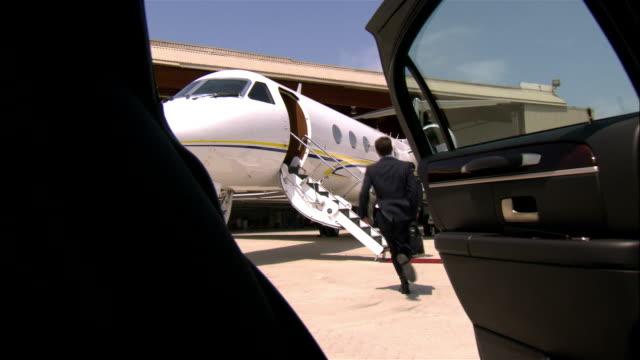 vidéos et rushes de close-up - wide shot businessman exiting limousine and running toward private airplane and pilot / long beach, california, usa - piste d'envol