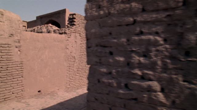 1999 Close-up - wide shot pan Men walking through ruins of ancient Citadel of Bam/ Bam, Kerman Province, Iran