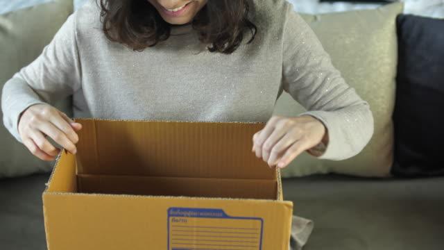 close-up, frau zu hause öffnet karton sitzend auf sofa - postangestellter stock-videos und b-roll-filmmaterial