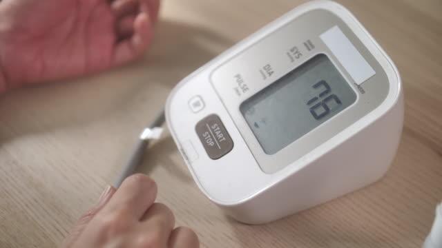自宅で血圧計をチェックするクローズアップ女性 - 血圧計点の映像素材/bロール