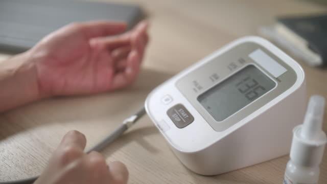 vídeos de stock, filmes e b-roll de close-up mulher verificando a pressão arterial - artéria