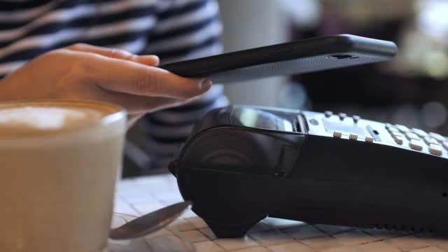 カフェでクローズアップ女性非接触支払い - モバイル決済点の映像素材/bロール