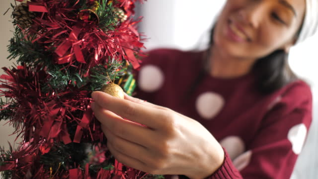 close-up woman decorating the christmas ball on the christmas tree at home - advent stock videos & royalty-free footage