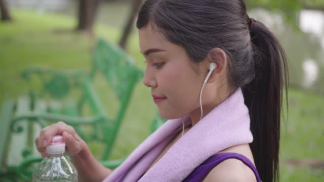 vídeos y material grabado en eventos de stock de close-up mujer beber agua después de actividades deportivas - mujeres jóvenes