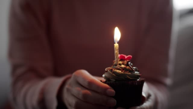 close-up woman hand holding a birthday cake or cupcake and put on the table. - birthday candle stock videos & royalty-free footage