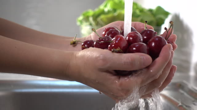 close-up woman hand washing fresh cherry under running water. rinsing ripe red cherries - faucet stock videos & royalty-free footage