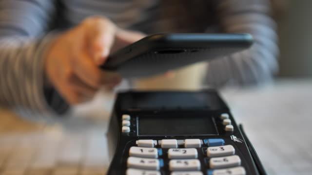 vídeos de stock, filmes e b-roll de close-up mulher pagando pagamento contactless com seu pone smart - estação