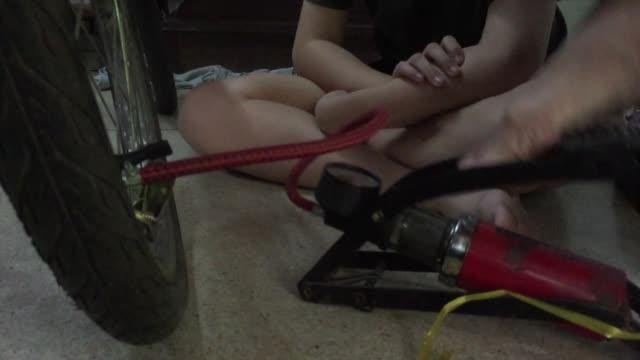 stockvideo's en b-roll-footage met closeup vrouw pompen lucht in de band van de platte fiets met luchtpomp - strak