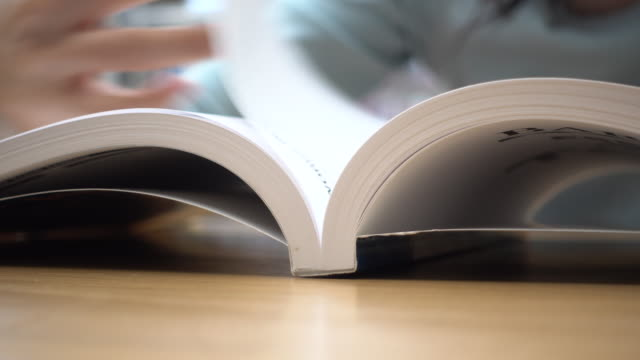 close-up woman reading and open book page - open book stock videos & royalty-free footage