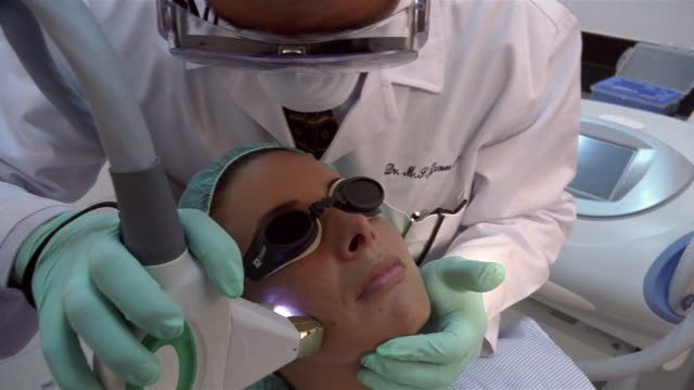 vídeos de stock e filmes b-roll de close-up woman receiving laser treatment from plastic surgeon/ panama city, panama  - tratamento a laser