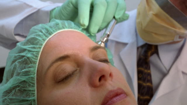 stockvideo's en b-roll-footage met close-up woman receiving laser treatment from plastic surgeon/ panama city, panama  - plastische chirurg