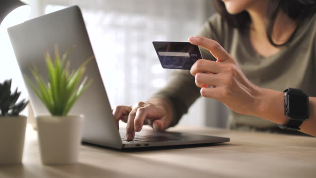 close-up donna shopping online sul suo laptop a casa - acquisto con carta di credito video stock e b–roll