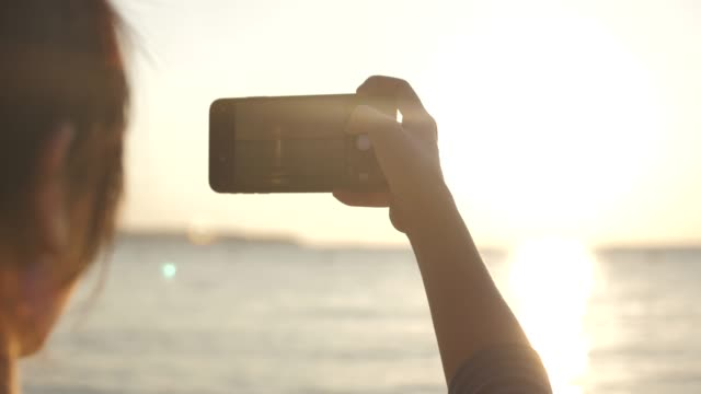 close-up woman taking sunset photo at beach - photograph stock videos & royalty-free footage