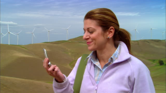 Close-up Woman talking on cell phone near wind turbines on hillside / Livermore, California, USA