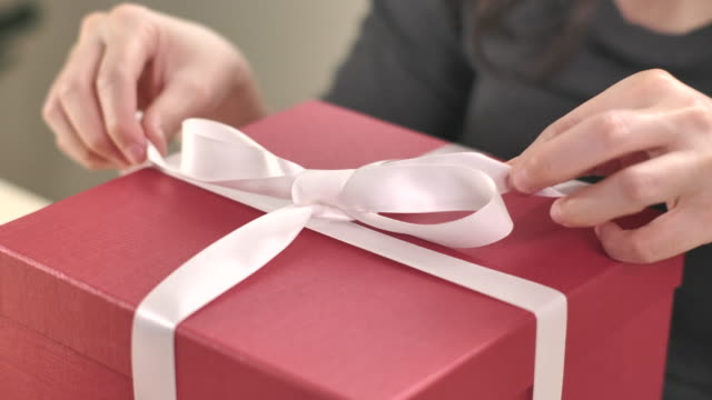close-up woman unwrap gift box and open gift box at home, slow motion - unwrapping stock videos & royalty-free footage