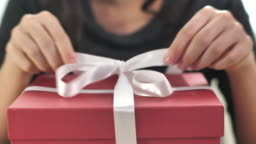 Close-up Woman unwrap Gift box and open gift box at home, Slow motion