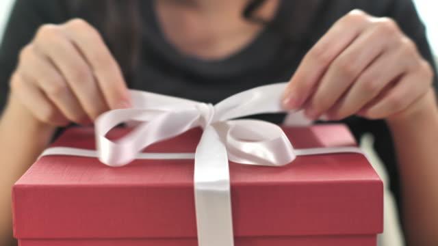クローズアップウーマンアンラップギフトボックスと自宅でギフトボックスを開く、スローモーション - 贈り物点の映像素材/bロール