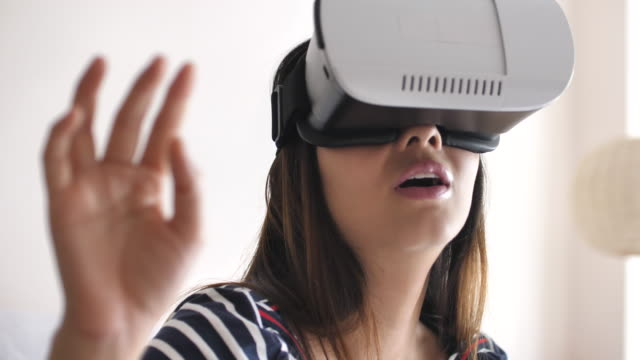 Close-up Woman using a virtual reality glasses at home, Slow motion