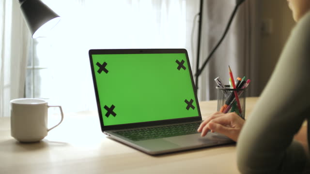 close-up woman using chroma key screen laptop computer on desk at home - green colour stock videos & royalty-free footage
