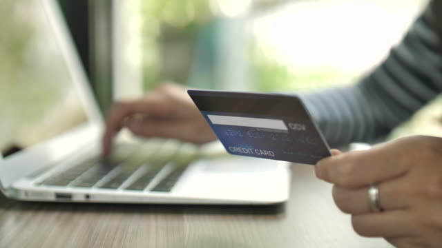 vídeos de stock, filmes e b-roll de close-up mulher usando cartão de crédito para compras on-line com laptop - sentando