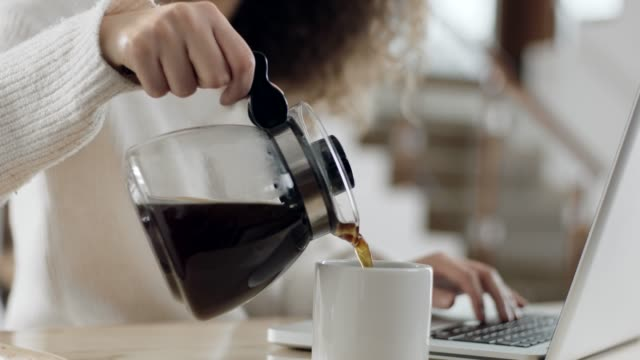 close-up, woman using laptop and pouring coffee in cup - oggetto creato dall'uomo video stock e b–roll