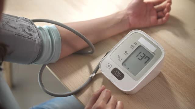 close-up woman using pressure blood pressure gauge machine checking blood pressure - examining stock videos & royalty-free footage