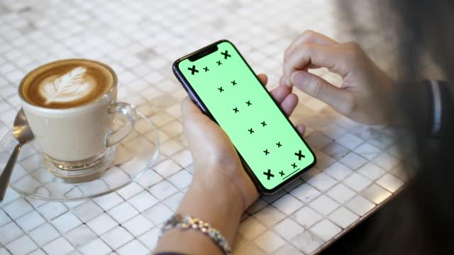 vídeos y material grabado en eventos de stock de primer plano mujer usando teléfono inteligente con pantalla verde - parte del cuerpo humano