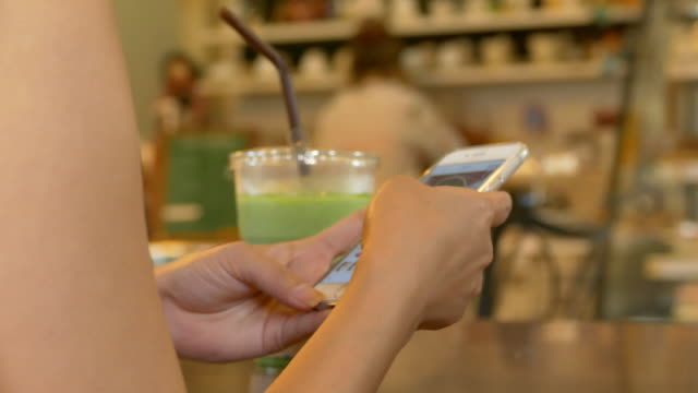 close-up woman using smartphone in restaurants. - froth art stock videos and b-roll footage