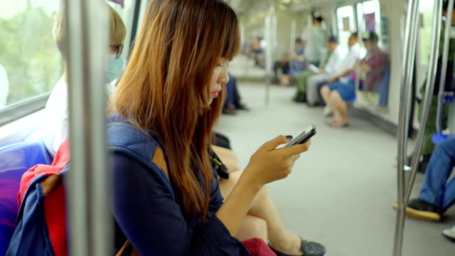 Close-up woman using smartphone on train