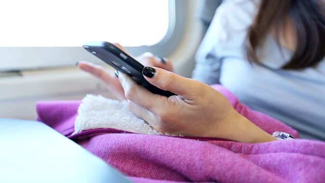 Primer plano de mujer usando teléfono inteligente en tren