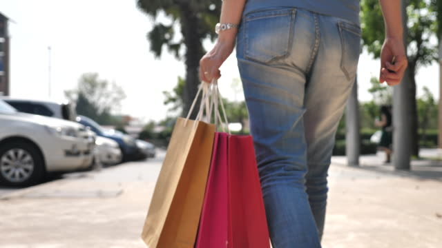 買い物の後にショッピングバッグで車に歩いているクローズアップ女性 - 駐車点の映像素材/bロール