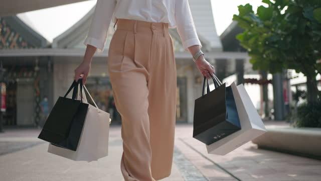 vidéos et rushes de femme de plan rapproché marchant avec le sac de sopping, ralenti - commerce